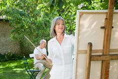 Mature woman painting at easel - stock photo