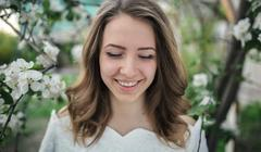 Headshot of smiling young woman in apple tree garden Stock Photos
