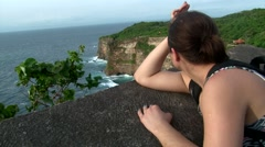 BALI. INDONESIA:  girl standing on the cliff and looking at the ocean in Temple Stock Footage