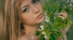 beautiful girl with a blooming branch closeup - stock footage