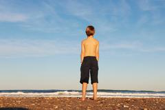 Boy on beach looking out to sea - stock photo
