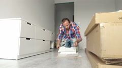 Troubled man with instruction trying to match pieces of furniture on floor at ho Stock Footage