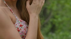 Girl corrects a dress and hair close up in the forest Stock Footage