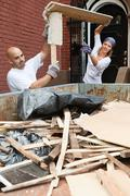 Couple filling skip with rubble - stock photo
