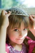 Girl putting on tiara Stock Photos