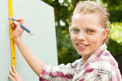Woman measuring plywood and marking with pencil - stock photo
