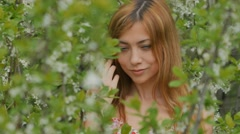 Girl closes her eyes among flowering branches Stock Footage