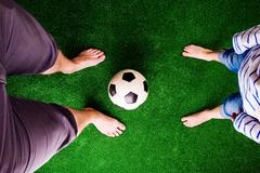 Father and son with soccer ball against green grass Stock Photos