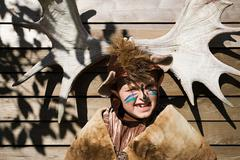 Boy dressed up as bear in front of moose antlers - stock photo