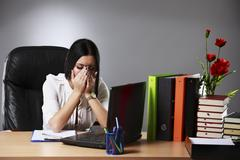 Frustrated young businesswoman analyzing chart during overtime Stock Photos