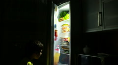 Child eating a snack in front of the refrigerator in the middle of the night. Stock Footage