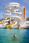 Man smiles in water at giant water slide Stock Photos