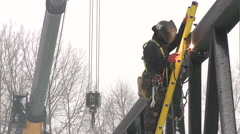 Worker welding bridge metal beam with a crane behind him Stock Footage
