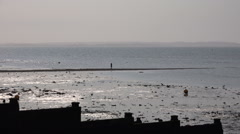 Whistable Beach U.K, View of lone person walking a narrow peninsula into the sea Stock Footage