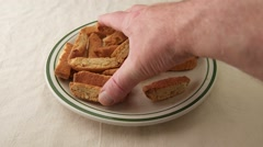 Almond nut biscotti being taken from plate Stock Footage
