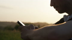 4K Close up of casual young man using his phone at sunset, in slow motion - stock footage