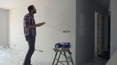 Young man painting wall and using tablet at his new home Stock Footage