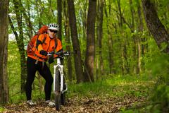 Cyclist Riding the Bike on a Trail in Summer Forest - stock photo