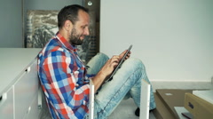 Young man using tablet while matching furniture on floor at home  Stock Footage
