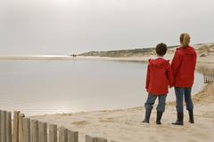 Mother and son looking out on beach - stock photo