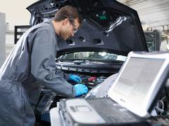 Mechanic working on engine analysis in car dealership workshop.  Laptop in - stock photo
