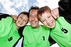 Father and sons team pep talk - stock photo