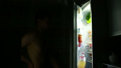 Man eating out of the refrigerator at night. hungry man Stock Footage