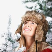 Woman with a faux-fur hat looking above Stock Photos
