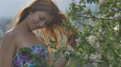 girl smiling near the blooming apple branch - stock footage