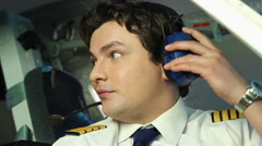Male pilot talking to crewmember, coordinating actions during flight, teamwork - stock footage