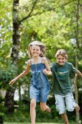 Boy chasing girl in garden Stock Photos