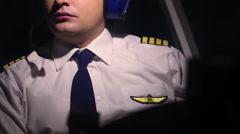 Man in civil aviation pilot uniform and headset navigating aircraft at cockpit - stock footage