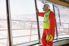 Older worker standing on guardrail - stock photo