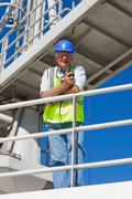 Harbour worker standing on guardrail - stock photo