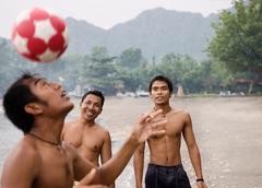 Guys playing football on beach Stock Photos