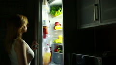 Woman opens the refrigerator at night. night hunger. diet. eating grapes - stock footage