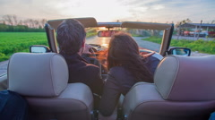 Middle-aged couple is driving together in an open-roof car Stock Footage