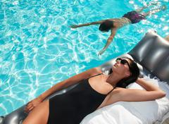 Woman tanning by the pool, man swimming Stock Photos