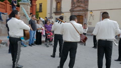A large group of mariachi band members play for tourists with audio Stock Footage