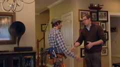 A contractor and home owner shake hands inside a house - stock footage
