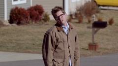 A depressed man walks away in suburbia Stock Footage