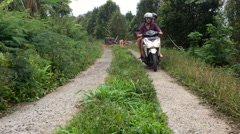 A skillful motorcycle rider driving in the mountains and jungles of Bali Stock Footage