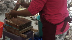 A woman makes hand made blue corn tortillas with a wooden press Stock Footage