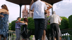 4 couples tango in el jardin with the parroquia in the background Stock Footage