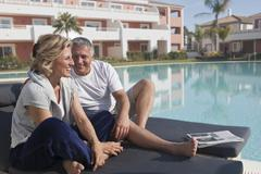 Mature couple on sunbeds by pool - stock photo