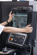 Engineer's hand on working computer panel of CNC machine - stock photo