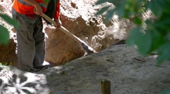 Road worker digs a trench Stock Footage