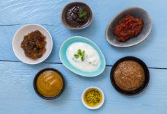 Variation of sauces and dips on wood background - stock photo