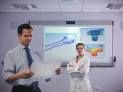 Scientists in front of product designs - stock photo