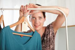 Woman holding clothing rail Stock Photos